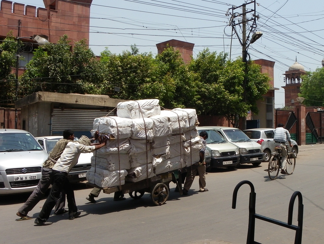 The Streets of Delhi, India. Men pushing a Cart.