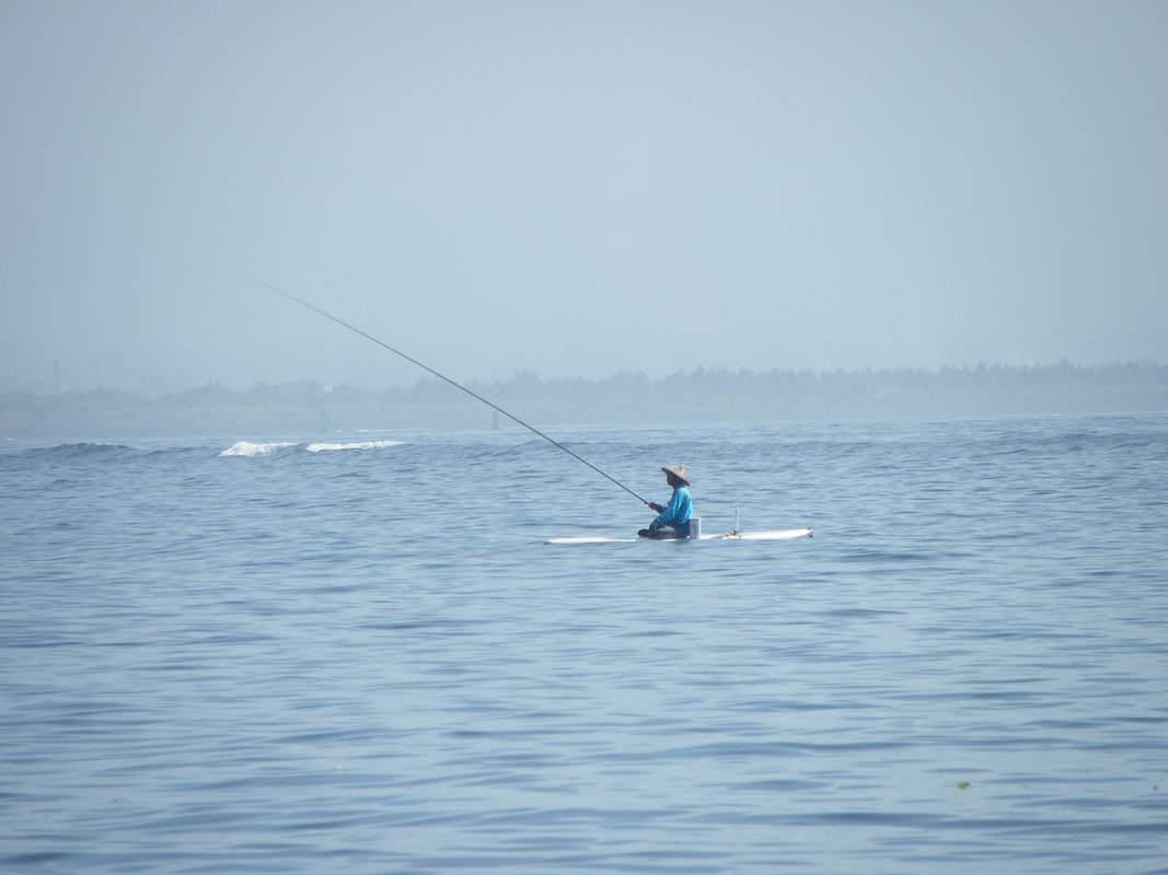 Fisherman on a surf board, Bali, Indonesia
