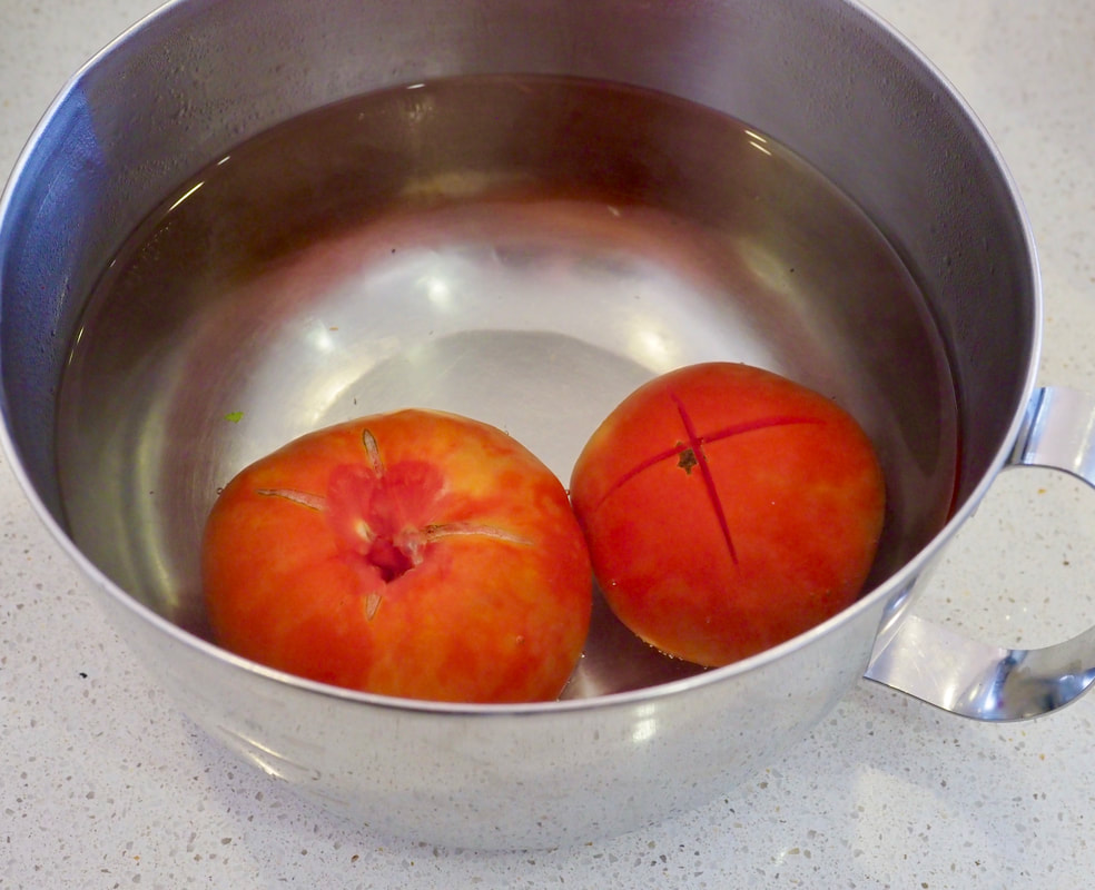 Tomatoes submerged in boiling water